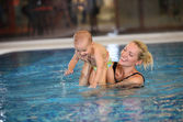 Young mother and little son having fun in a swimming pool — Stock Photo