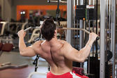 Rear view of young fitness guy working out on exercise machine — Stock Photo