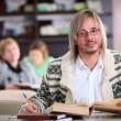 Handsome man studying at desk with lots of books — Stock Photo #19225121