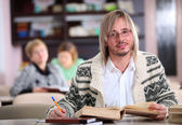 Yakışıklı adam masa kitap ile öğrenim — Stok fotoğraf
