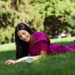 Cheerful young girl lying on grass in park, reading magazine - Stock Photo