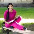 Cheerful young girl sitting on bench in park, reading magazine — Foto de Stock