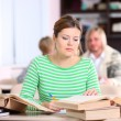 Young woman studying at desk with lots of books — Stock Photo #19920325