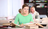 Young woman studying at desk with lots of books — Foto Stock