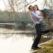 Young couple having fun on river beach in early spring - Stock Photo