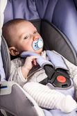 Cute little boy wearing a seat in the child car seat — Stock Photo