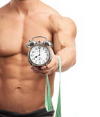 Cropped view of a muscular young man holding clock and measuring tape. It is high time for workout concept. — Stock Photo