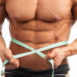 Cropped view of young muscular man with measuring tape around his waist — Stock Photo