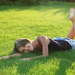 Beautiful young woman lying down on grass — Stock Photo