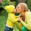 Little boy kissing his mother outdoors — Stock Photo
