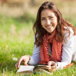 Young girl reading book while lying on grass — Stock Photo