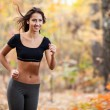 Happy woman running in autumn forest — Stock Photo