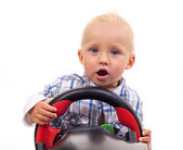 Little boy holding a toy steering wheel over white — Stock Photo