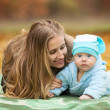 Foto Stock: Womwith baby in autumn park