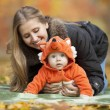 Young woman with baby dressed in fox costume — Stock Photo
