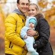 Young couple with baby boy in autumn park — Stock Photo
