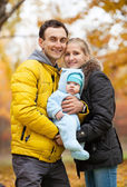 Young couple with baby boy in autumn park — Stockfoto