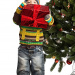 Cute little boy with gift near Christmas tree — Foto Stock