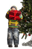 Cute little boy with gift near Christmas tree — Stok fotoğraf