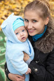 Young woman and her baby son in autumn park — Stock Photo