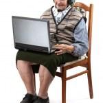 Senior woman using laptop computer over white — Stock Photo