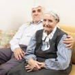 Mature man and senior woman sitting on sofa — Stock Photo