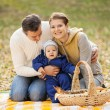 Young couple with baby boy on picnic in autumn — Stock Photo
