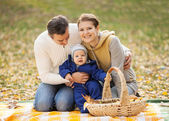 Young couple with baby boy on picnic in autumn — Stockfoto