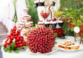Sweet bar with berries and cakes — Stock Photo