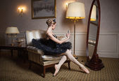 Ballerina in black tutu sitting in front of mirror — Stock Photo