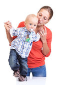 Baby boy learning to walk with mother's help — Stock Photo