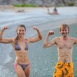 Young woman and man flexing their muscles jokingly — Stock Photo #41358265