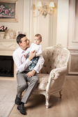 Young man with son sitting in living room — Stock Photo