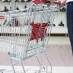 Woman pushing shopping cart in shoe store, close-up — Stock Photo #4294250