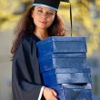 Young female graduate with stack of boxes — Stock Photo #4294498