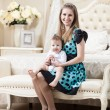 Woman with little son sitting on couch in bedroom — Stock Photo