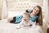 Mother and baby son having fun on bed at home — Stock Photo