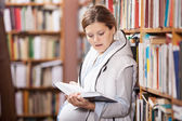Young pregnant woman reading book in library — Stock Photo