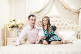 Young happy family with a baby on bed — Stock Photo