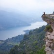 Young man sitting on edge of cliff — Stock Photo #47580593