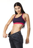 Young woman in old jeans pants after losing weight — Stock Photo