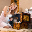 Pregnant woman looking into case with baby clothes — Stock Photo #4769174