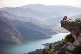 Female hiker sitting on cliff and enjoying valley view — Stock Photo