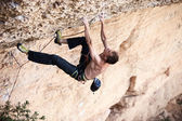 Rock climber on his challenging way up — Stock Photo