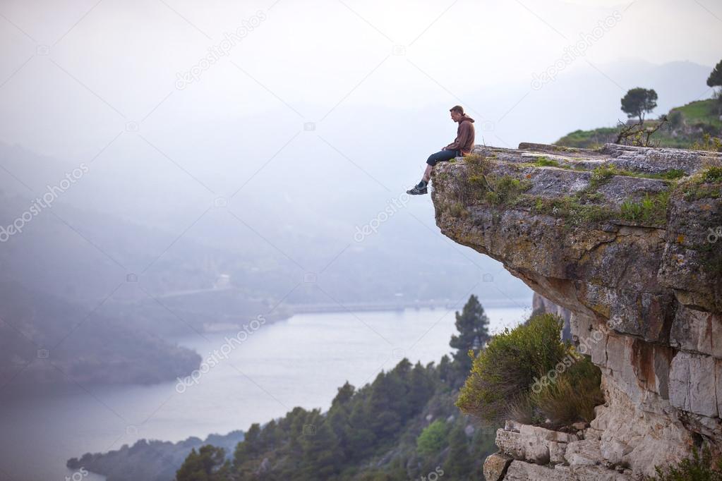 jeune homme assis sur le bord de la falaise et en regardant la rivi re ci dessous photographie. Black Bedroom Furniture Sets. Home Design Ideas