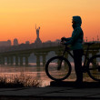 Young woman with bicycle against sky at sunset — Stock Photo #7533552