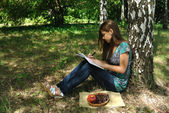 A girl reads a book in public garden — Stockfoto