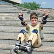 The jolly boy with roller blades sitting at the steps — Stock Photo