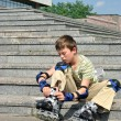 The boy with roller blades resting at the steps — Stock Photo