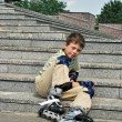 The tired boy with roller blades rests at the steps — Stock Photo
